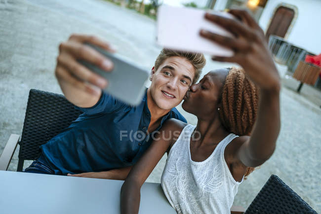 Young couple taking selfies at outdoor cafe — Stock Photo