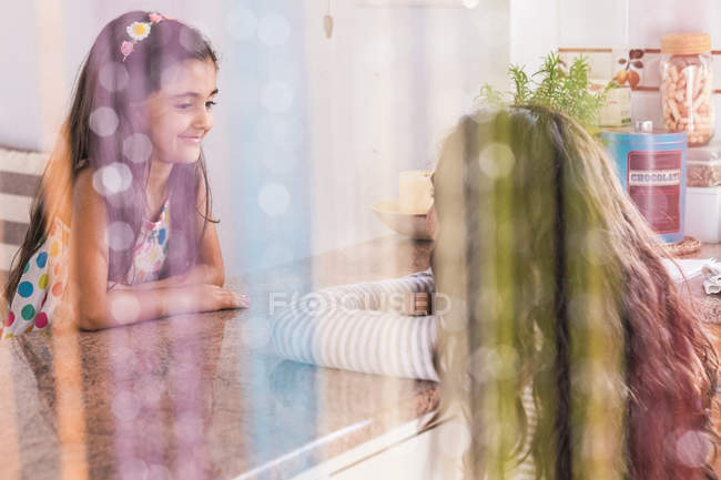 Teenage girl and her little sister in kitchen — Stock Photo