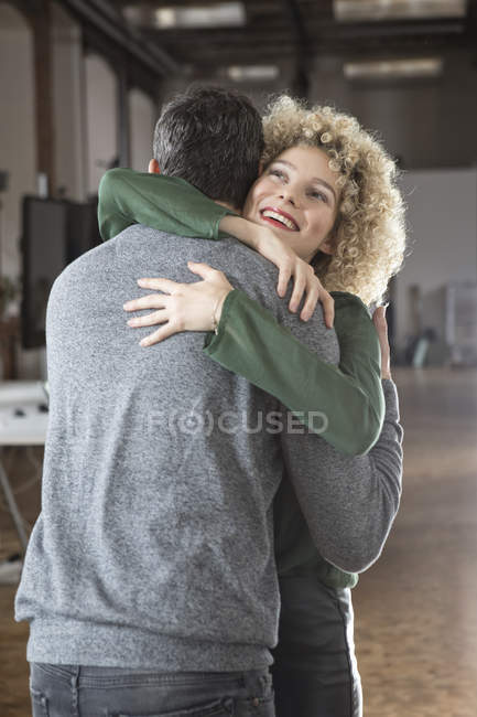 Happy man and woman hugging in office — Stock Photo