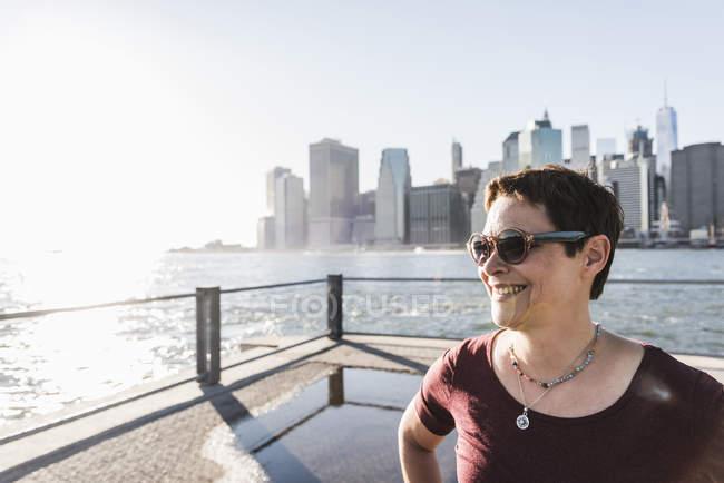 Donna in piedi davanti allo skyline di Manhattan — Foto stock