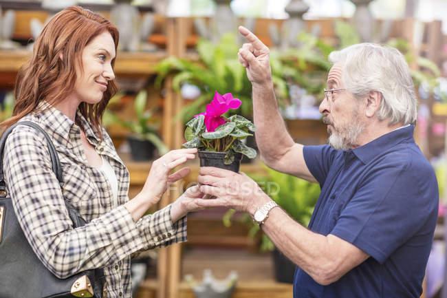 Gardener helping woman at garden centre — Stock Photo