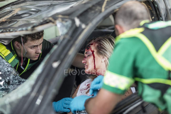 Paramedics helping car crash victim after accident — Stock Photo