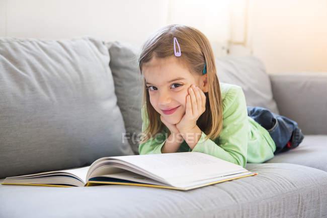 Portrait d'une petite fille souriante allongée sur un canapé avec un livre — Photo de stock