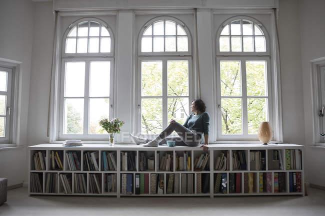 Donna che guarda fuori dalla finestra mentre seduto sul davanzale della finestra a casa — Foto stock