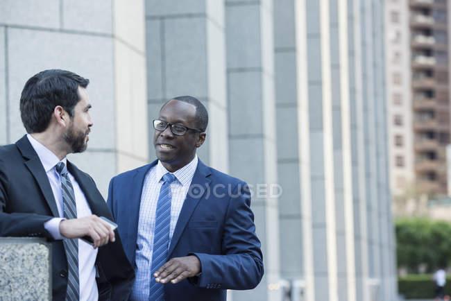 Два улыбаясь бизнесменов говорить на открытом воздухе — стоковое фото