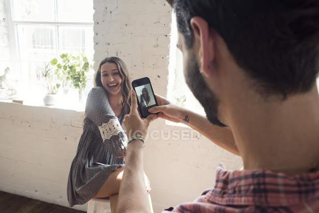 Mulher jovem feliz posando para um celular de tiro — Fotografia de Stock
