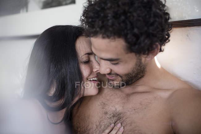 Glückliches, liebevolles Paar, das sich im Bett umarmt — Stockfoto