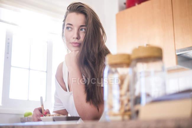 Молода жінка в кухні мислення — стокове фото
