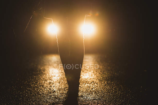 Headlights shining on legs of a woman at night — Stock Photo