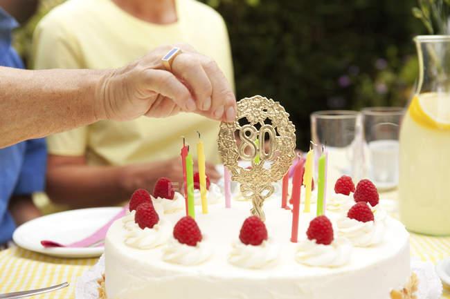 Руки removimg 80-день рождения украшения от торт — стоковое фото
