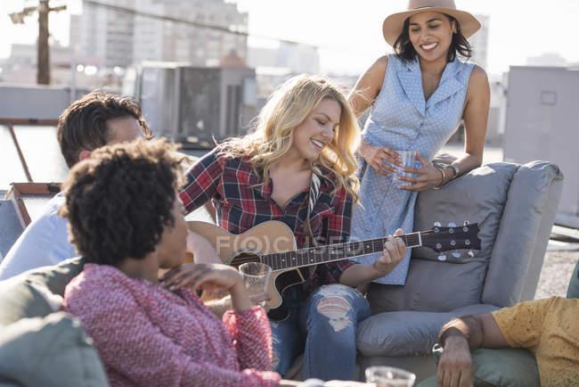 Женщина играет на гитаре для друзей на вечеринке на крыше, Лос-Анджелес, США — стоковое фото