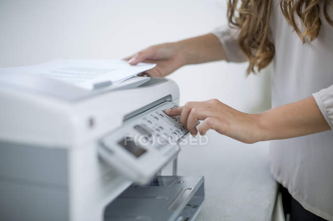 Female hands using printer in office — Stock Photo