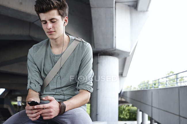 Teenage boy with cell phone and earbuds outdoors — Stock Photo