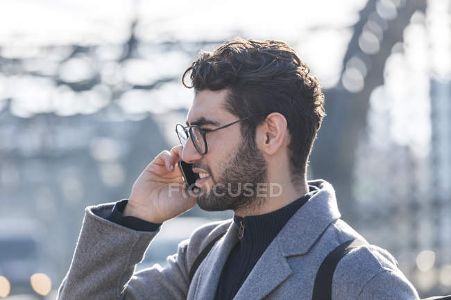 Portrait of young businessman with backpack on the phone — Stock Photo