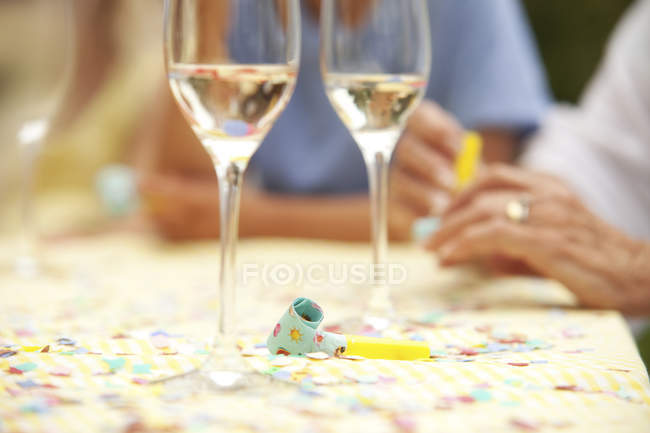 Party blowout and glasses of champagne on table — Stock Photo