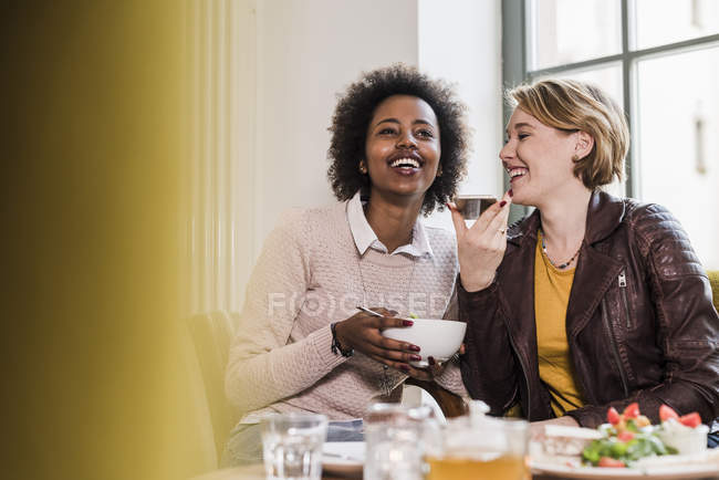 Two young women with cell phone meeting in a cafe — Stock Photo