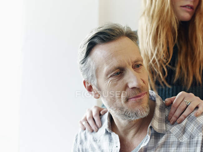 Mature man and young woman with hands on his shoulders — Stock Photo