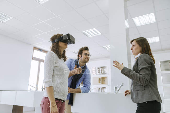 Couple in plumbing shop getting customer consultation, woman in virtual reality glasses — Stock Photo