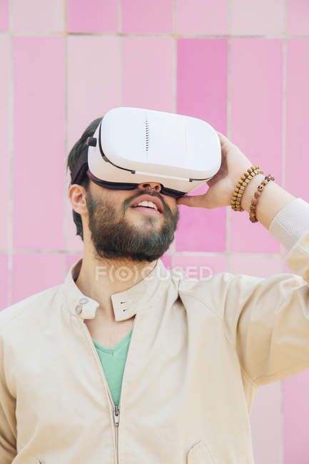 Человек в очках виртуальной реальности перед розовой стеной — стоковое фото