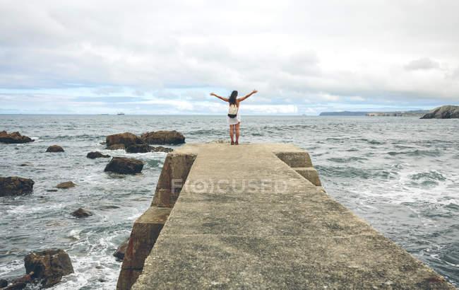 Женщина с распростертыми объятиями, стоя на пирсе — стоковое фото