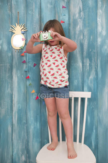 Lttle girl satnding on chair playing with vintage toy camera — Stock Photo