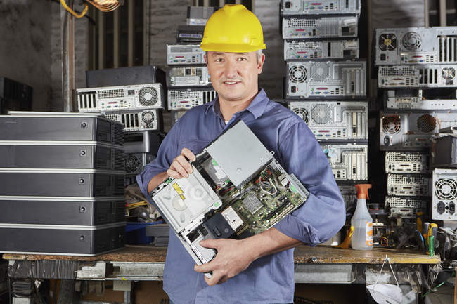 Worker in computer recycling plant carrying pc casing — Stock Photo