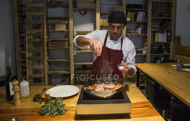 Man gießt Salz auf rinderbäckchen in einer Pfanne mit sautierten Gemüse — Stockfoto