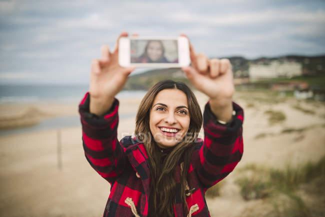 Glückliche junge Frau unter einem Selfie am Strand — Stockfoto