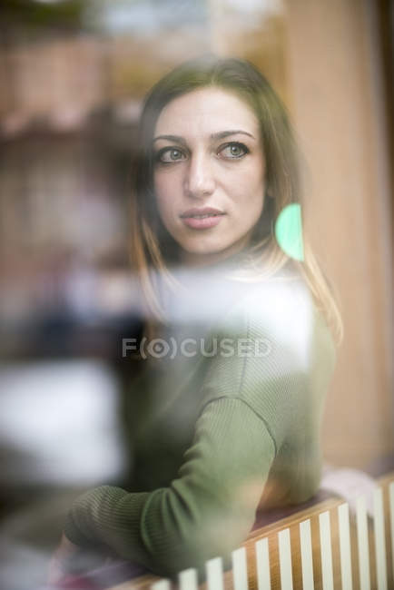 Young woman sitting in coffee shop, looking through window — Stock Photo