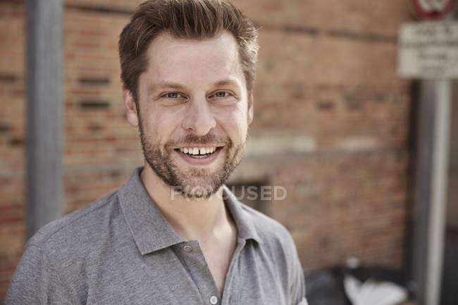 Porträt eines lächelnden Mannes, der in die Kamera blickt — Stockfoto