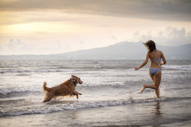 Mexico, Nayarit, Young woman in bikini playing with her Golden Retriever dog at the beach — Stock Photo
