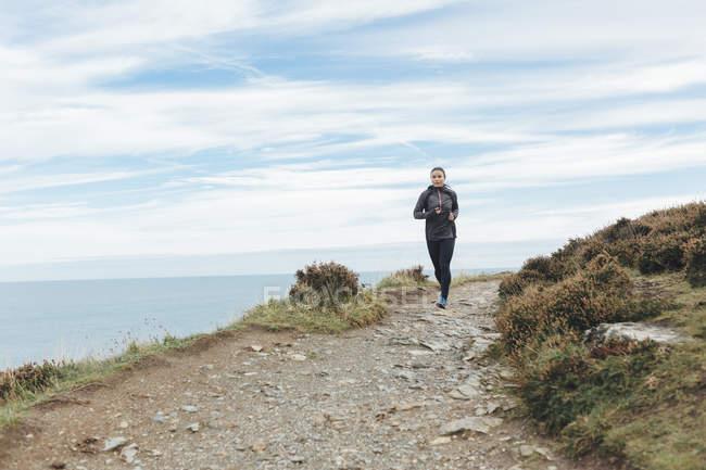 Ирландия, Ходжсон, женщина, бегущая по прибрежной дорожке — стоковое фото