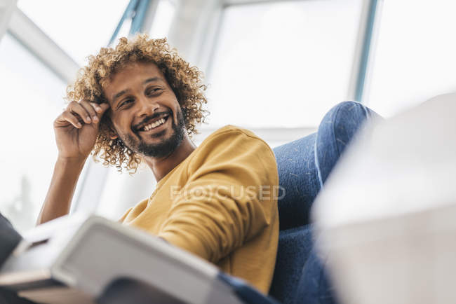 Smiling young man with Afro hairstyle sitting in armchair — Stock Photo