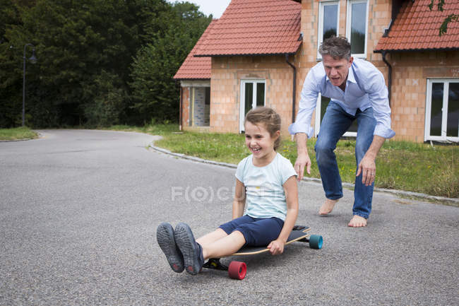 Father and daughter longboarding in garden — Stock Photo