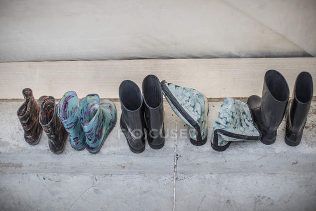 Row of rubber boots on stone surface — Stock Photo