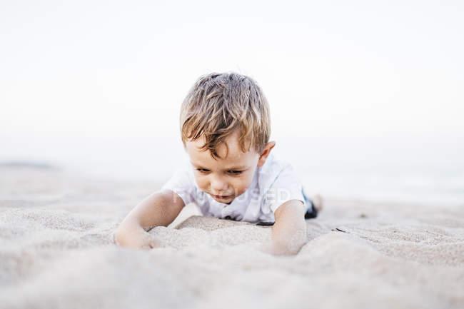 Cute caucasian little boy having fun on sandy beach — Stock Photo