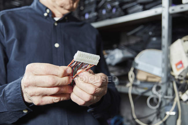 Cropped image of man holding motherboard connector — Stock Photo