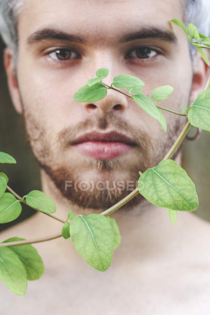 Portrait of young man behind fern leaves twigs of honeysuckle — Stock Photo