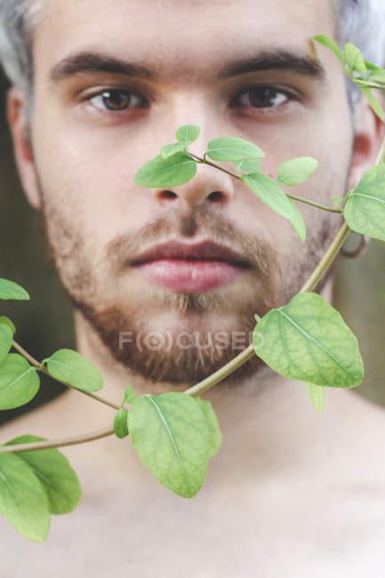 Ritratto di giovane dietro le foglie di felce ramoscelli di caprifoglio — Foto stock