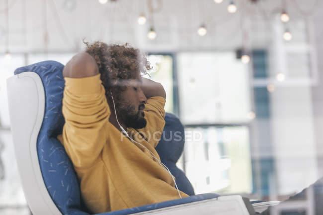 Молодой человек расслабляется в кресле с закрытыми глазами и с наушниками — стоковое фото