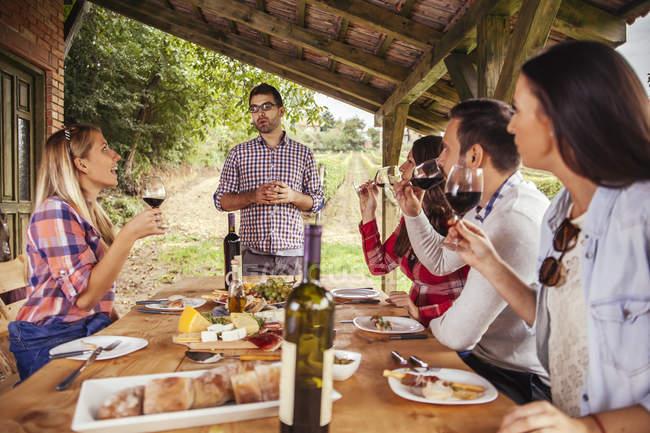 Людина, даючи мови відкритий столом стежать друзів — стокове фото