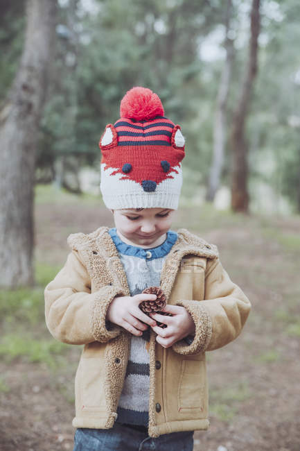 Boy wearing woolly hat holding pine cone in forest — Stock Photo
