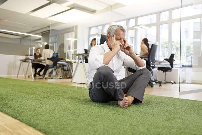 Adult caucasian Businessman meditating in office — Stock Photo