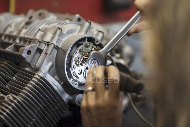 Close-up of Mechanic working on motorcycle engine in workshop — Stock Photo