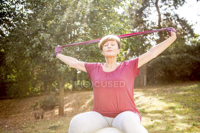 Senior woman on gymnastics ball stretching with scarf in sunshine garden — Stock Photo