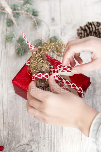Hands of girl wrapping Christmas present, closeup — Stock Photo