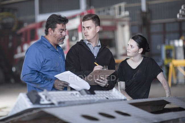 Mechanics working at fire brigade workshop reading check list — Stock Photo