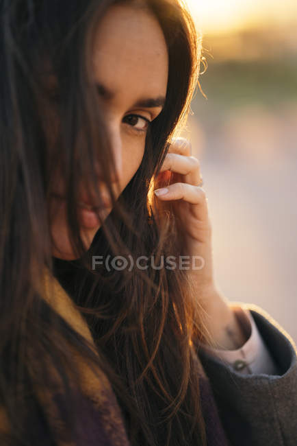 Portrait of woman with brown hair standing at sunset — Stock Photo