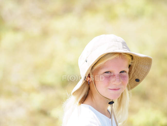 Portrait of a blond girl wearing a floppy hat — Stock Photo