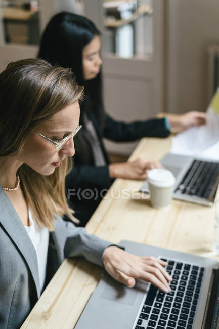 Two business women working together in office — Stock Photo